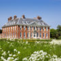 South front of the house from the meadow with white flowers at Uppark House and Garden, West Sussex.